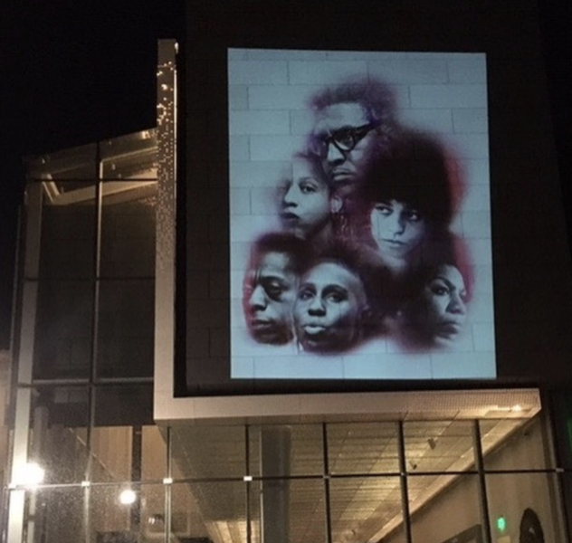 The faces of Black Queer artists projected onto the Asheville Art Museum in Downtown Asheville